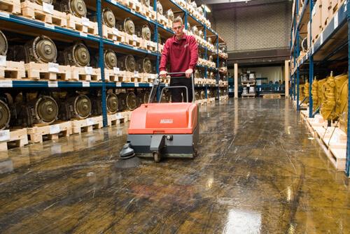 Schilten Schoonmaak medewerker machinaal aan het vegen in een magazijn