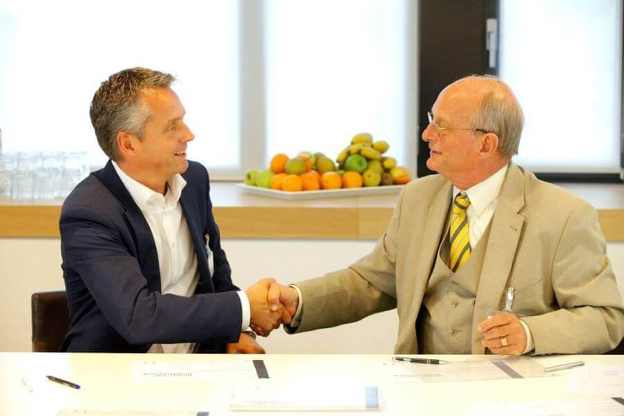 Twee volwassen heren schudden elkaar de hand na het tekenen van een overeenkomst met een fruitschaal op de achtergrond