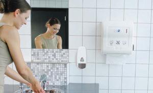 Vrouw was haar handen in een schone toiletruimte