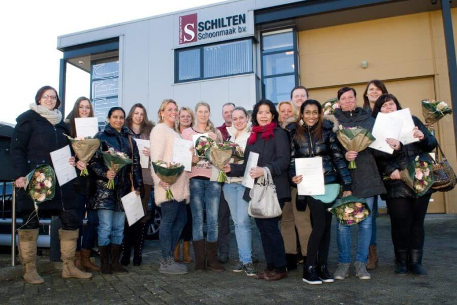 Groepsfoto van het Schilten personeel voor het Schilten Schoonmaak bedrijfspand, met bossen bloemen